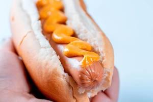 Nahaufnahme von Hotdog mit Senf in der Hand einer Person