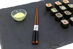 Nahaufnahme von japanischen Essstänchen mit Sushi und Wasabi
