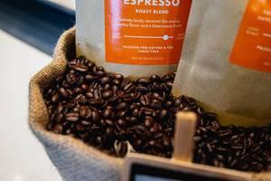 Nahaufnahme von Kaffee in Papiertüten auf gerösteten Kaffeebohnen in Jutesack