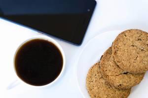 Nahaufnahme von Keksen und Kaffee mit Smartphone auf weißem Hintergrund