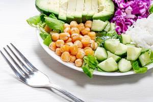 Nahaufnahme von Kichererbsen mit geschnittenem Gemüse und Reis auf einem Teller