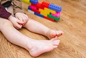 Nahaufnahme von Kinderbeinen auf dem Boden neben Spielzeug