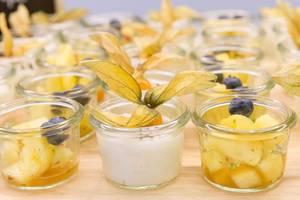 Nahaufnahme von kleinen Frühstückssnacks in Gläsern, mit Klebreis, Kokosmilch und Sesamkernen und eingelegte Ananas in süß-sauer Sauce