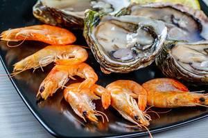 Nahaufnahme von Königsgarnelen und frischen Austern auf einem schwarzen Teller