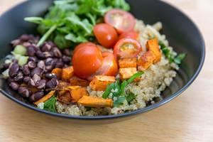 Nahaufnahme von kubanischer Quinoa-Bowl mit Süßkartoffeln, Cherry-Tomaten, Rukola und roten Bohnen