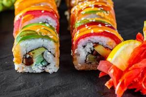 Nahaufnahme von kunstvoll hergestellten, bunten Sushirollen mit Käse und Lachs