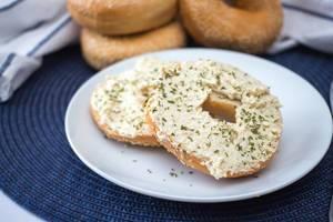 Nahaufnahme von mit Frischkäse bestrichenem Bagel verfeinert mit Kräutern auf Teller