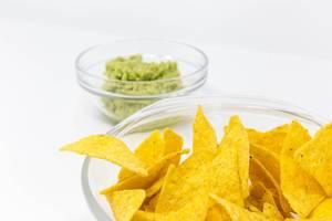 Nahaufnahme von Nacho Chips mit Guacamole Avocado Dip im Hintergrund