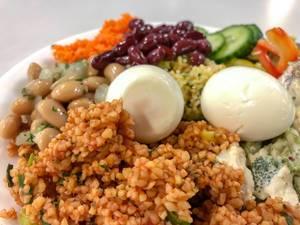 Nahaufnahme von nahrhaftem Salat mit Couscous, ganzem Ei, Bohnen, Gurken und Karotten