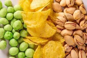 Nahaufnahme von Partysnacks wie Wasabi-Erdnüssen, Kartoffelchips und Pistazien