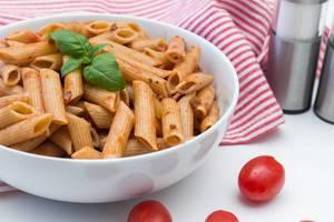 Nahaufnahme von Pasta mit Tomatensoße, dekoriert mit frischem Basilikum
