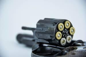 Nahaufnahme von Patronen in Revolvertrommel – geladene Waffe vor weißem Hintergrund