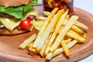 Nahaufnahme von Pommes Frites auf einem Holzbrett, mit Cheeseburger und eisgekühltem Getränk im Hintergrund