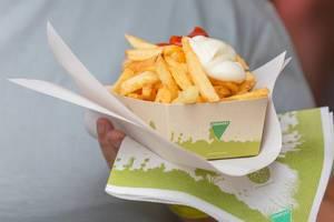 Nahaufnahme von Pommes Frites rot-weiß mit Ketchup und Mayonnaise in Pappschale