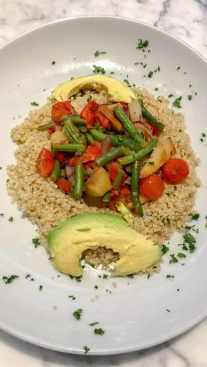 Nahaufnahme von Quinoa mit blanchiertem Gemüse und Avocado