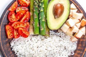 Nahaufnahme von Reis mit Chiasamen, Obst und Gemüse auf einem Bambusteller
