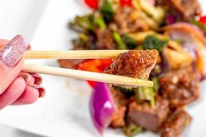 Nahaufnahme von Rindfleisch zwischen zwei Essstäbchen und Gemüse im Hintergrund