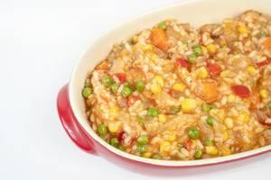 Nahaufnahme von Risotto mit Erbsen, Mais, Tomaten, Karotten und Paprika