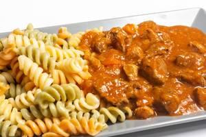Nahaufnahme von saftigem Gulasch mit dreifarbiger Pasta auf grauem Teller