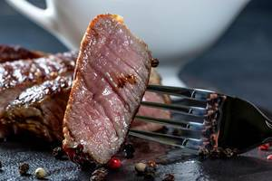 Nahaufnahme von saftigem Stück Steak auf Gabel, im Hintergrund Steak, Pfefferkörner und Sauciere