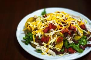 Nahaufnahme von Salatteller, bestehend aus Karotten, Tomaten, Bohnen und Blattsalat