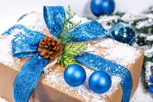 Nahaufnahme von schneebedecktem Weihnachtsgeschenk in Naturpapier und blauer Schleife, geschmückt mit Tannenzapfen