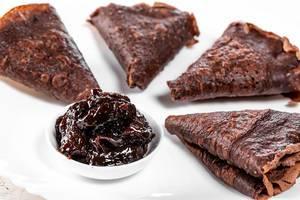 Nahaufnahme von Schokoladen-Pfannkuchen, zu Dreiecken gefaltet, mit Mus in einer weißen Schale