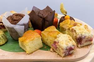 Nahaufnahme von Schokoladenmuffins und verschiedenen Stücken Obstkuchen auf einem Küchenbrett am Büfetttisch des AXA Barcamps OMWest 2019 in Köln