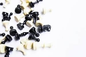 Nahaufnahme von schwarzen und weißen Schachfiguren liegend auf weißem Hintergrund
