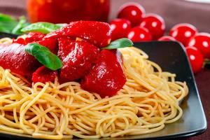 Nahaufnahme von Spaghetti-Nudeln mit roter Paprika und Tomatensauce