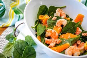 Nahaufnahme von Spinat-Salat mit Garnelen und Orange