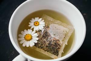 Nahaufnahme von Teebeutel mit Kamillentee in einer weißen Tasse von oben fotografiert