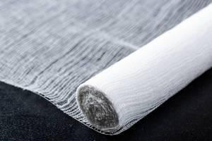Nahaufnahme von teilweise aufgerollter Bandage oder Verband auf dunklem Hintergrund