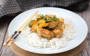 Nahaufnahme von Tofu in Soße mit Bandnudeln aus Reis