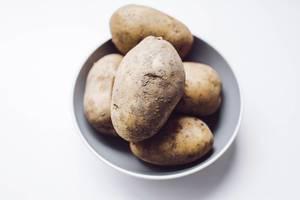 Nahaufnahme von ungeschählten, rohen Kartoffeln in einer Schale auf weißem Hintergrund