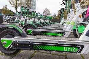 Nahaufnahme von unten: viele ordentlich geparkte Lime E-Scooter in Köln