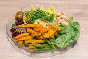 Nahaufnahme von veganem Salat auf Glasteller mit Edamame, Blumenkohl, Spinat, Rote Beete, Pilze und Zucchini