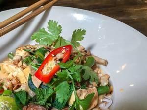 Nahaufnahme von veganes Tofu-Pilz Gericht mit grünes Topping auf weißem Teller