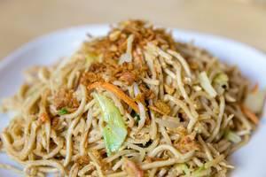 Nahaufnahme von vegetarischen  asiatischen Nudeln, gebratenem Gemüse und Eier-Sauce, auf einem weißen Teller auf einem Holztisch