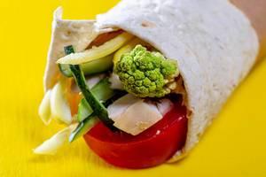 Nahaufnahme von vorne auf mit Gemüse und Fleisch gefülltes Fladenbrot vor gelbem Hintergrund