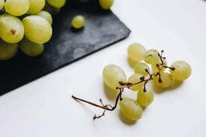 Nahaufnahme von weißen Weintrauben vor weißem Hintergrund
