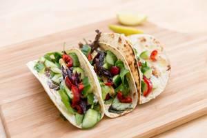 Nahaufnahme von würzig-feurige Halloumi-Tacos mit roter Zwiebel, roter Chili, Gurke und Salatmischung