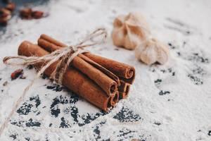 Nahaufnahme von Zimtstangen auf verstreutem Mehl