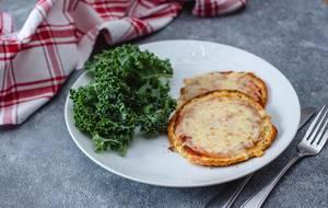 Nahaufnahme von zwei Pizza-Törtchen, neben grünen Blättern auf einem weißen Teller auf dem Küchentisch