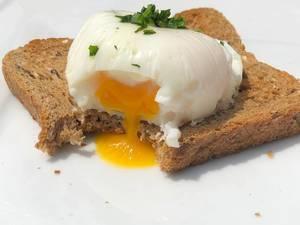 Nahaufnahme zeigt ein angebissenes pochiertes Ei auf Vollkornbrot, mit flüssigem Eigelb, auf einem weißen Tisch, als vegetarische Frühstücksidee