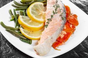 Nahaufnahme zeigt ein fertiges Stück Lachs mit Gemüse, Thymian und Zitronenscheiben auf einem weißen Teller, mit schwarzer Schiefersteinplatte im Hintergrund