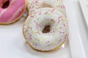 Nahaufnahme zeigt einen Donut mit weißer Glasur und pinken Streuseln, auf einem weißen Tablett