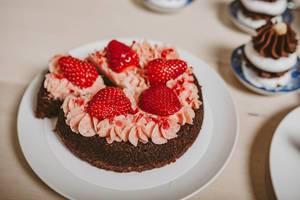 Nahaufnahme zeigt einen Erdbeerkuchen mit roter Sahne, als Dessert