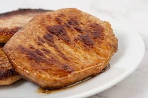 Nahaufnahme zeigt fertiges, gebratenes Schweinefleisch auf einem Teller