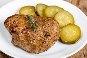 Nahaufnahme zeigt gebackenes Stück Fleisch neben Gewürzgurken